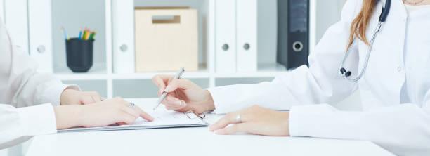 Junger Arzt erklärt, wie eine medizinische ausfüllen, Patientin. Partnerschaft, Vertrauen und Medizinethik Konzept – Foto