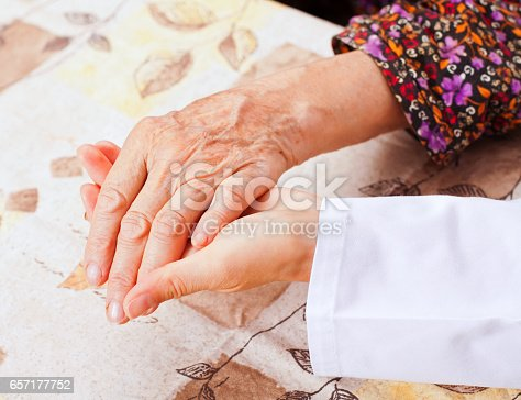 499062115istockphoto Young doctor holds the elderly woman hands 657177752
