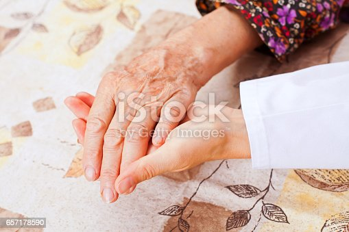 499062115istockphoto Young doctor holds the elderly woman hands 657178590