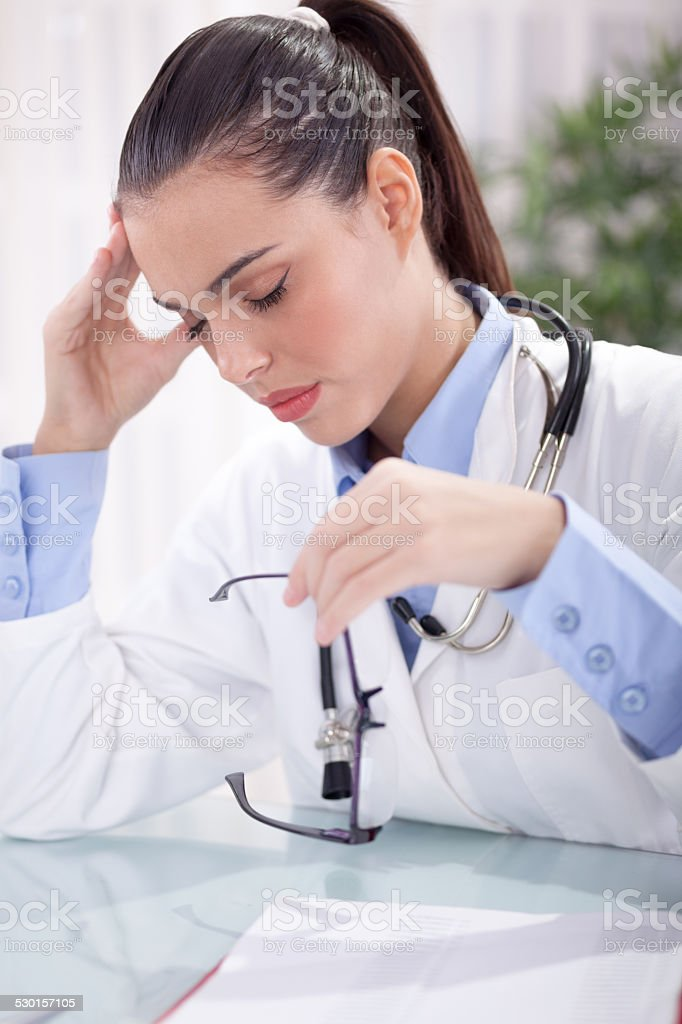 young doctor in a stressful situation has a headache stock photo