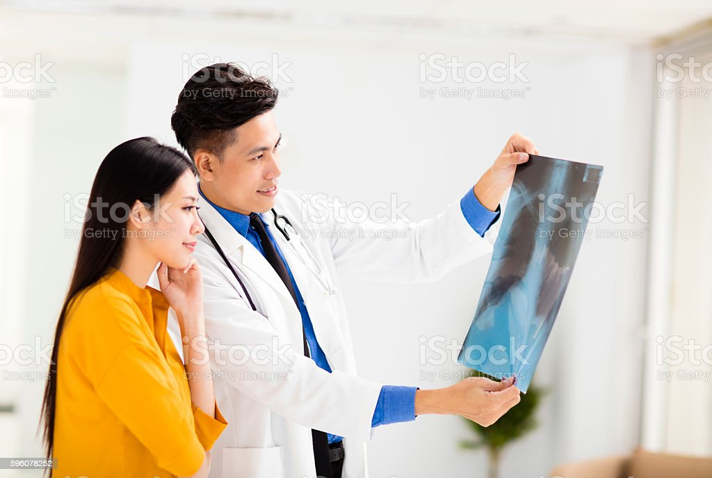 young doctor looking at patient's x-ray film royalty-free stock photo