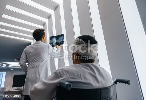 Healthcare professional young doctor examining and  analyzing x-ray CT Scan test of human head results of the patients skull with his patient in a medical hospital clinic.