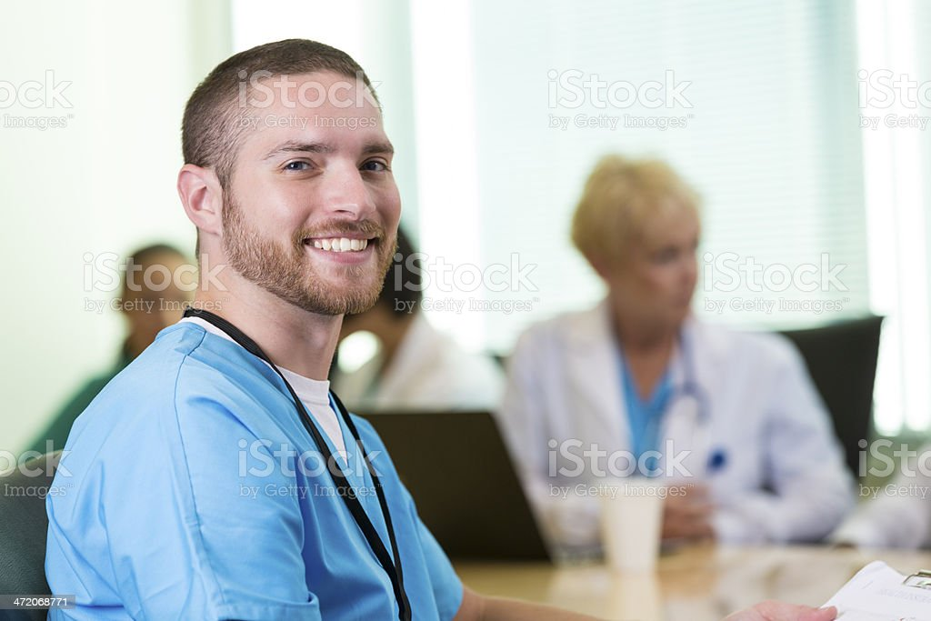 Young doctor or medical intern smiling before meeting in hospital stock photo
