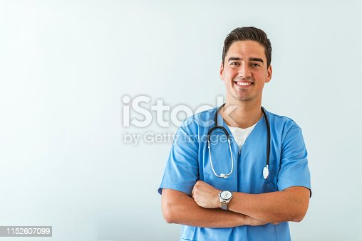 Portrait of a smiling doctor. Doctor with stethoscope standing, crossed arms, isolated on bright background. Portrait of a friendly doctor smiling at the camera.