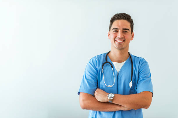 Young doctor Portrait of a smiling doctor. Doctor with stethoscope standing, crossed arms, isolated on bright background. Portrait of a friendly doctor smiling at the camera. assistant stock pictures, royalty-free photos & images