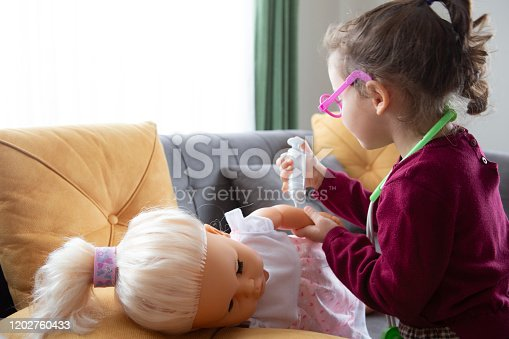 little girl as a doctor and playing a doll at home