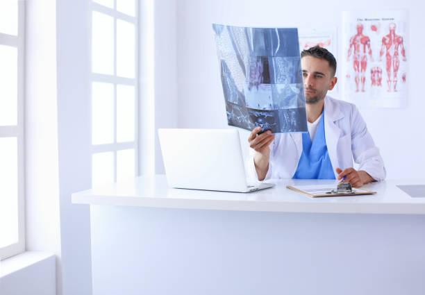 Junger Arzt sitzt an seinem Schreibtisch und Analyse einer Röntgenaufnahme – Foto