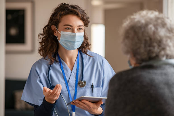 Young doctor visits senior woman with surgical mask stock photo