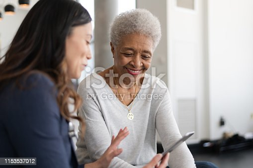 A young doctor and an elderly patient are indoors at the woman's home. The doctor is talking to the woman while holding a tablet computer. They're both smiling.