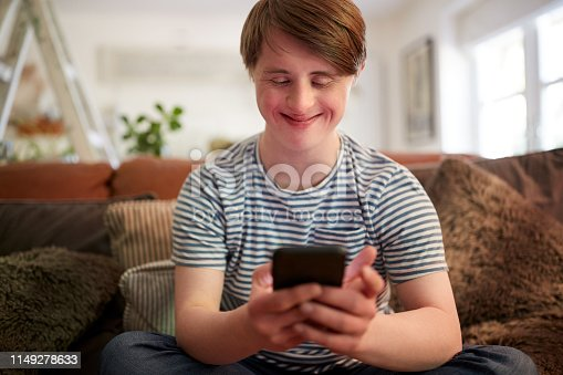 istock Young Downs Syndrome Man Sitting On Sofa Using Mobile Phone At Home 1149278633