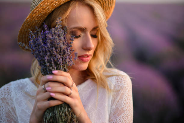 Young dreamy woman with bouquet in her hands standing in flowering lavender field stock photo