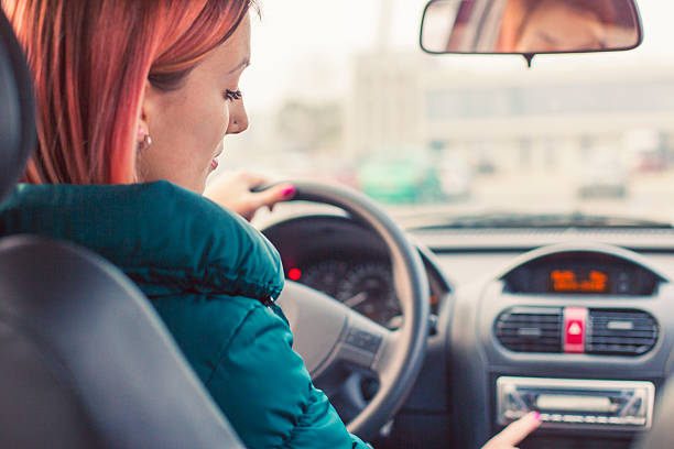 young driver changing radio stations - radio station stock photos and pictures