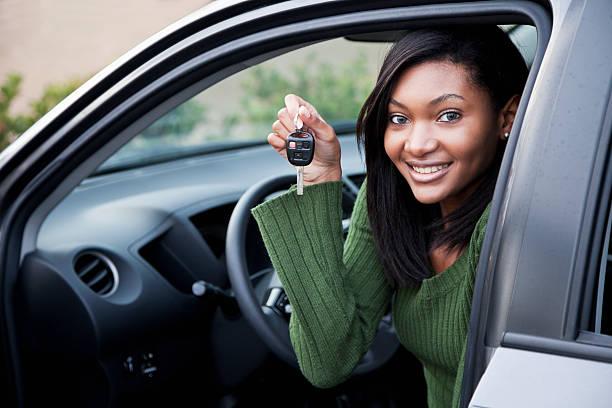 junger fahrer hält sich autoschlüssel - autos für fahranfänger stock-fotos und bilder