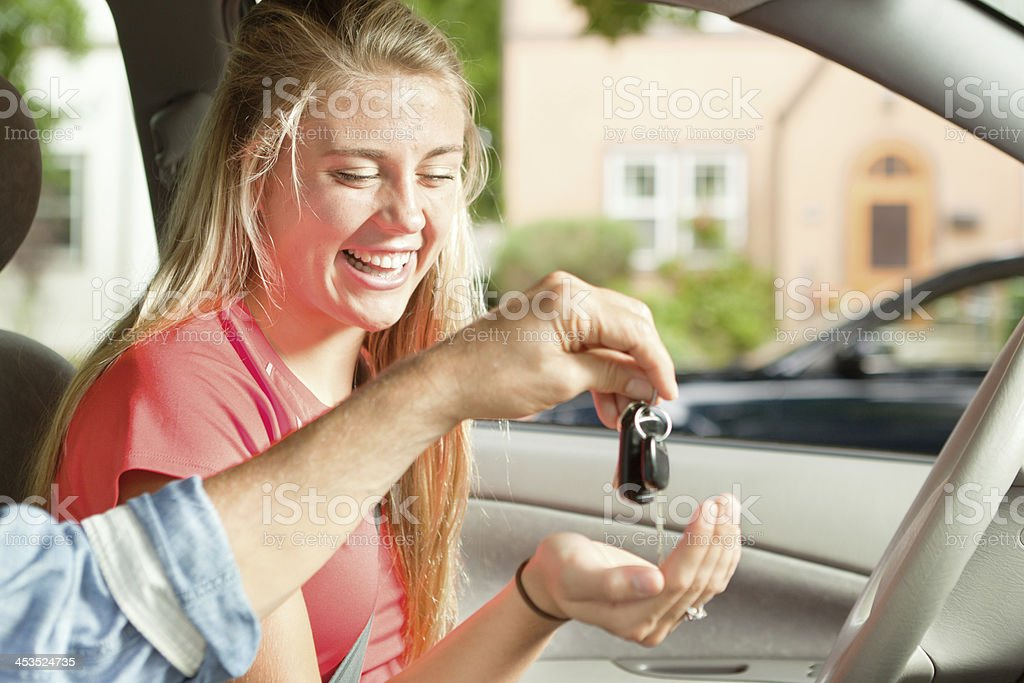Young Driver Receiving Car Key from Parent Sitting in Vehicle stock photo