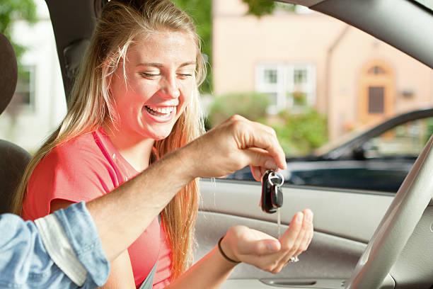 junger fahrer empfangen autoschlüssel von eltern sitzen im auto, - autos für fahranfänger stock-fotos und bilder
