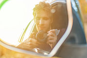 young driver taking a self portrait with professional camera in the car window