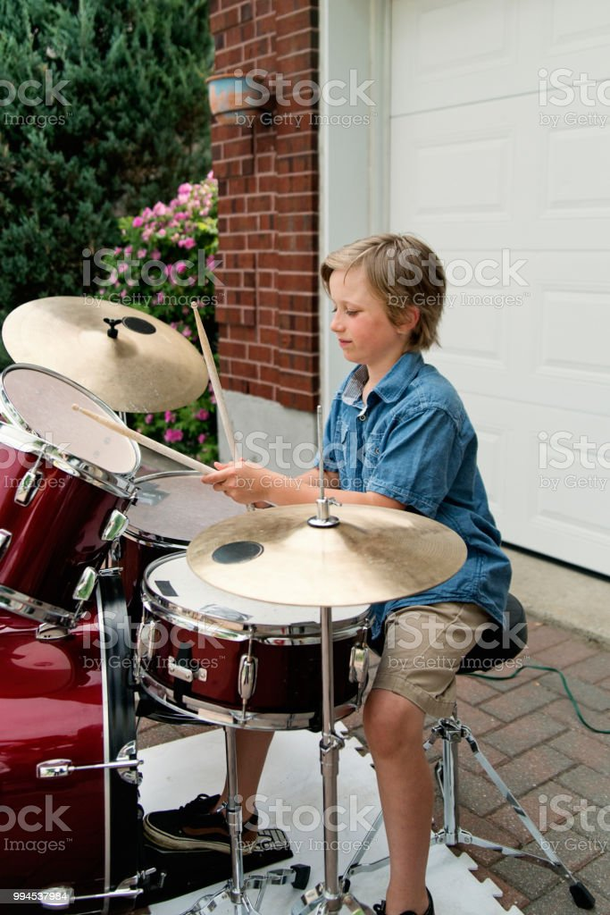 Young drummer rehearsing before show in family driveway. stock photo