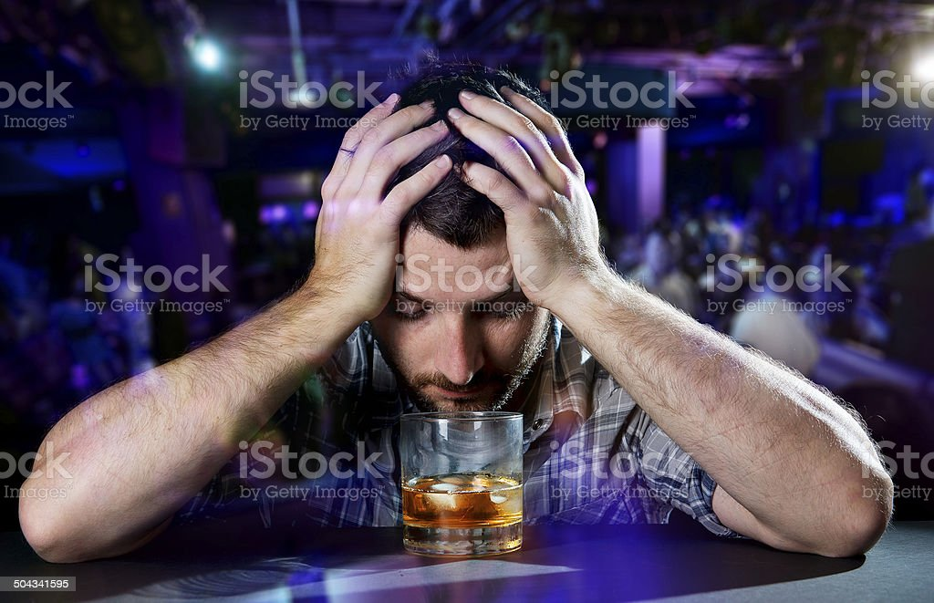 young drunk man depressed drinking whiskey at disco nightclub stock photo