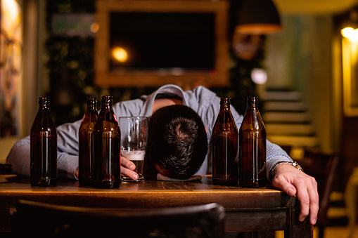 Young drunk man sleeping on bar counter