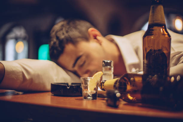 young drunk man sleeping on bar counter - drunk stock photos and pictures