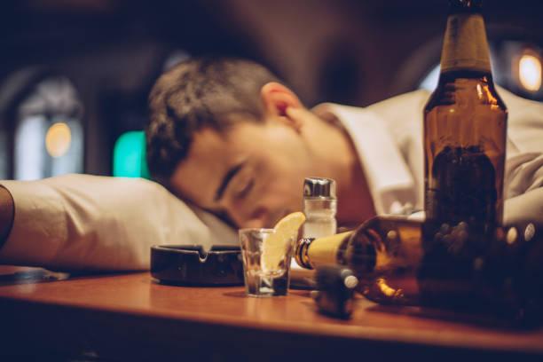 Jeune homme ivre dormant sur comptoir - Photo