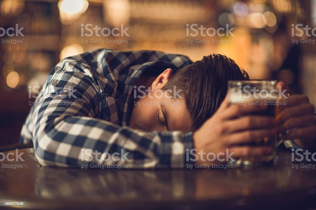 Young drunk man sleeping on the table in a bar. stock photo
