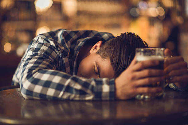 young drunk man sleeping on the table in a bar. - drunk stock photos and pictures