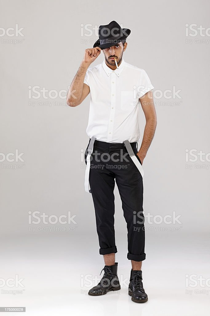 Young dude with a cigarette posing on grey background stock photo