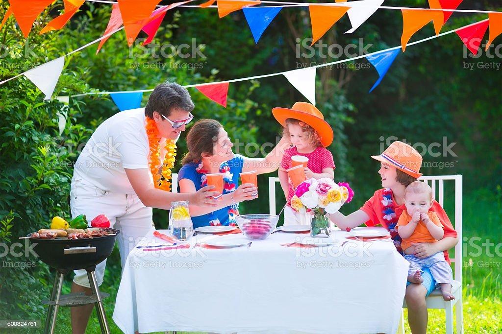 Jeune famille néerlandaise a grill fête dans le jardin - Photo