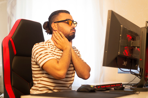 Young e sports player has neck and joint pain at the computer.