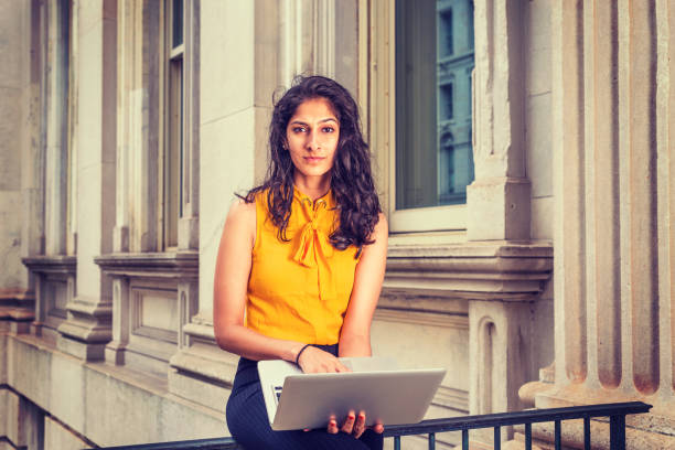 Young East Indian American Business Woman working in New York East Indian American Business Woman in New York. Wearing sleeveless orange shirt, a college student sitting by office building, working on laptop computer, thinking. students with laptop stock pictures, royalty-free photos & images