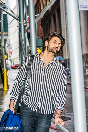istock Young East Indian American Man with beard traveling in rainning day in New York City 1143768133