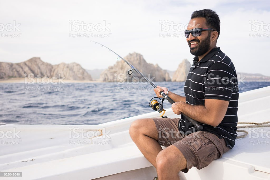 Young East Indian man fishing on open water. stock photo