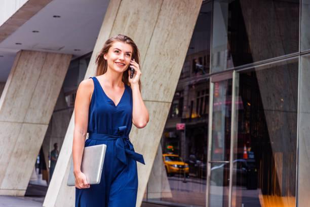 young östlichen europäischen amerikanerin reden über handy, reisen, arbeiten in new york city - jumpsuit blau stock-fotos und bilder