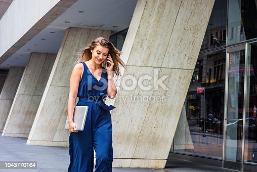 Young Eastern European American Woman talking on cell phone, traveling, working in New York City, wearing blue sleeveless jumpsuit, carrying laptop computer, walking on street outside office building.