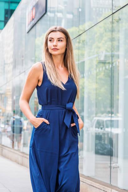 junge östliche europäische frau mit langen braunen haaren, die in new york city reisen - jumpsuit blau stock-fotos und bilder
