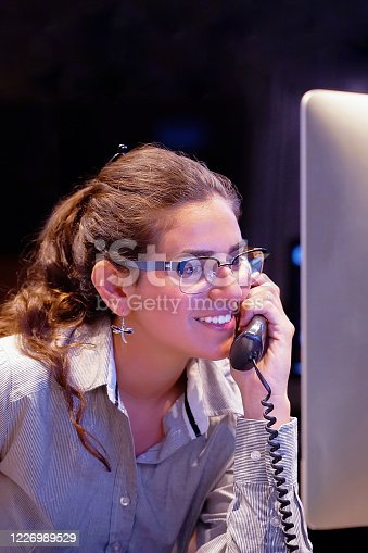 1167562098 istock photo Young efficient secretary working in the office, she is answering phone calls. Customer service concept. Night time. 1226989529