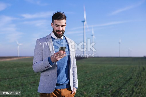 Electric engineer outdoors in front of windmills. Shallow DOF. Developed from RAW; retouched with special care and attention; Small amount of grain added for best final impression.16 bit Adobe RGB color profile.