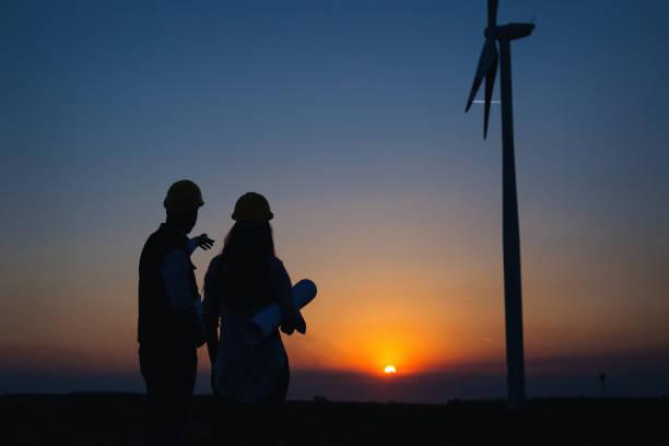 Junge Ingenieure electric im Freien vor Windmühlen – Foto