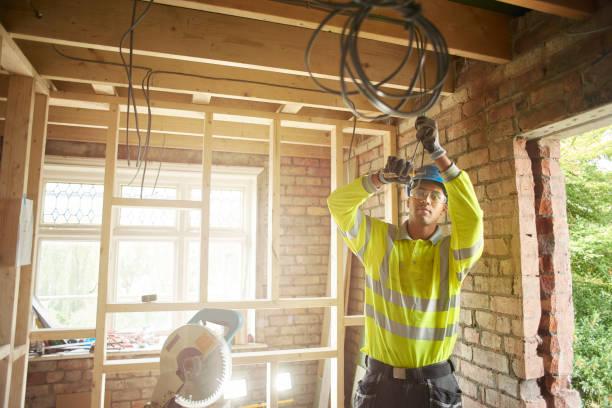 joven electricista en sitio - electricista fotografías e imágenes de stock