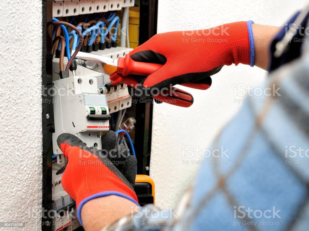 保護手袋と電気パネルの仕事で若い電気工事技術者 ロイヤリティフリーストックフォト