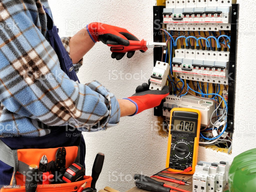 Young electrician technician at work on a electrical panel with protective gloves stock photo