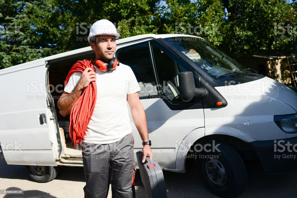 young electrician worker taking tools out of professional truck van​​​ foto
