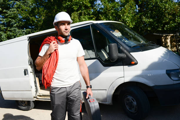 young electrician worker taking tools out of professional truck van – Foto