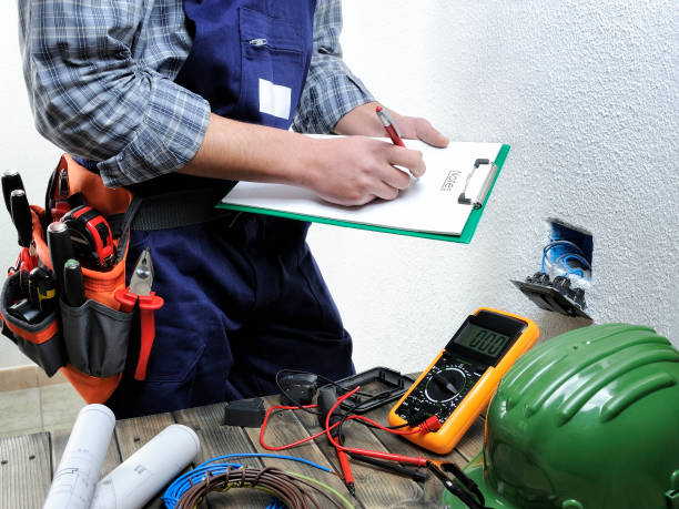 Young electrician working in a residential electrical installation stock photo