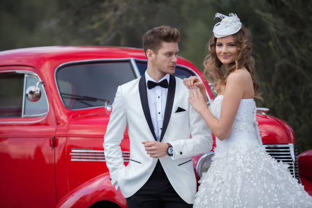 junge eleganz brautpaar am retro-auto - bräutigam anzug vintage stock-fotos und bilder