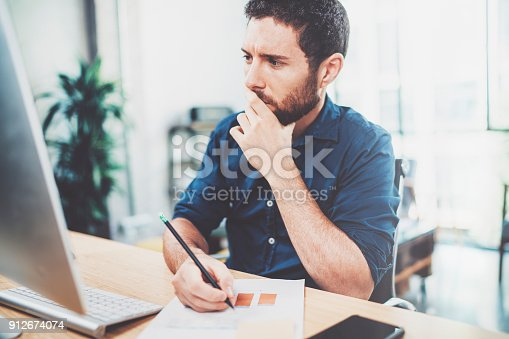 istock Young elegant banking finance analyst working at sunny office on laptop while sitting at wooden table.Businessman analyze stock reports.Blurred background,horizontal. 912674074