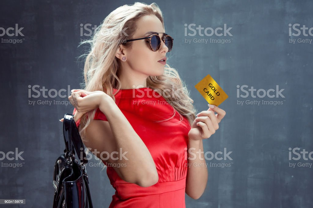 Young elegant blonde with bag on her shoulder holds gold card stock photo