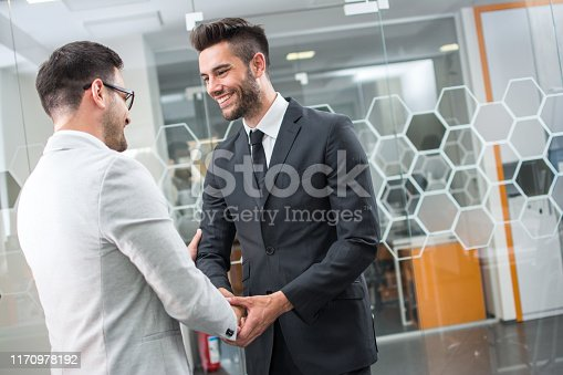859896852istockphoto Young elegant businessman shaking hand of client after negotiating and signing contract at indoor meeting 1170978192