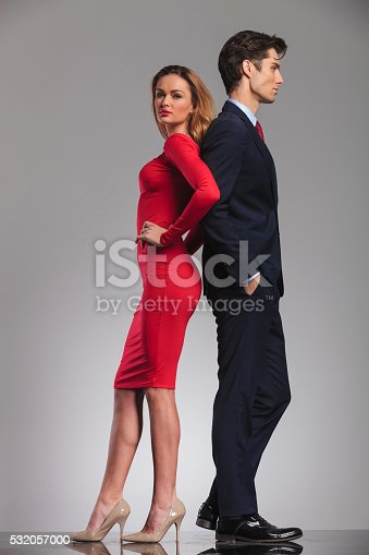 istock young elegant couple standing back to back in studio 532057000